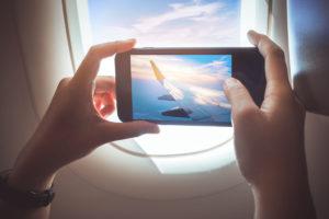 Kuvituskuva: Ihminen kuvaa lentokoneen ikkunasta maisemaa.