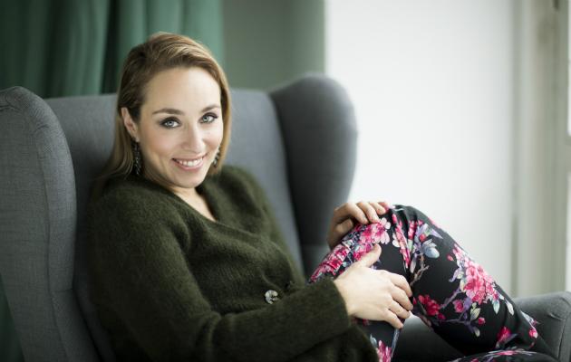 Anni Hautala poseeraa sohvalla.