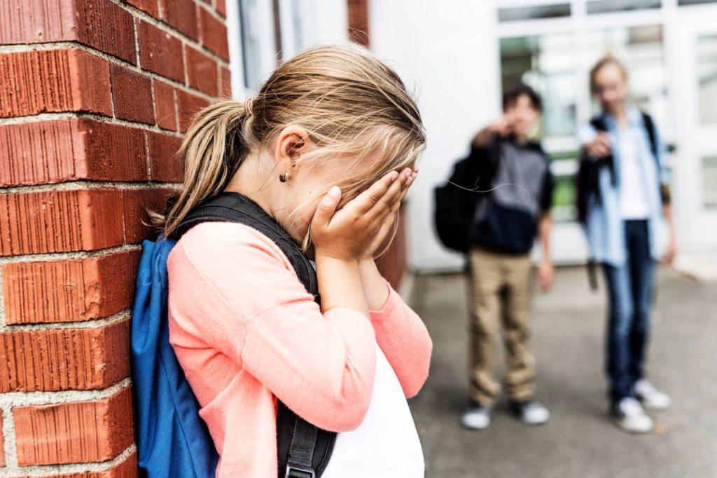Kuvituskuva: Tyttö itkee koulun kulmalla.