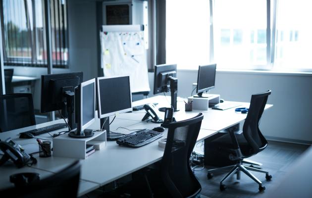 Toimiston työpöydät ammottavat tyhjyyttään.
