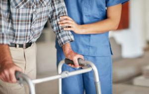 Hoitaja auttaa rollaattorin kanssa kulkevaa vanhusta. Kuvituskuva.