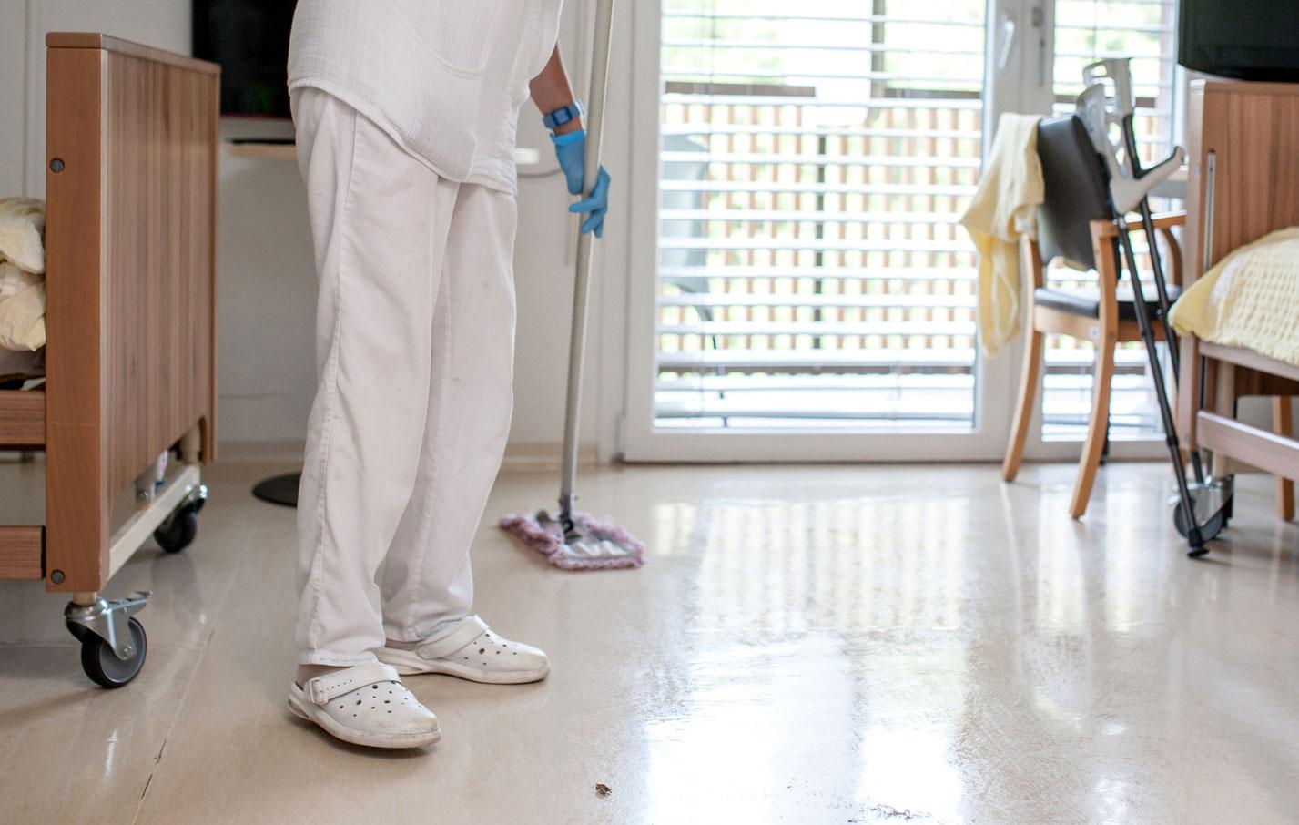 Hoitaja siivoaa lattiaa