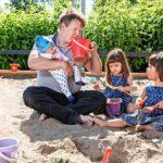 """Isällä on aikaa leipoa hiekkakakkuja Ansan (kesk.) ja Elinan kanssa. Raimon sylissä on perheen kuopus Inka. """"En ole kasvattajana niin määrätietoinen kuin nuorempana, enkä stressaa pienistä."""""""
