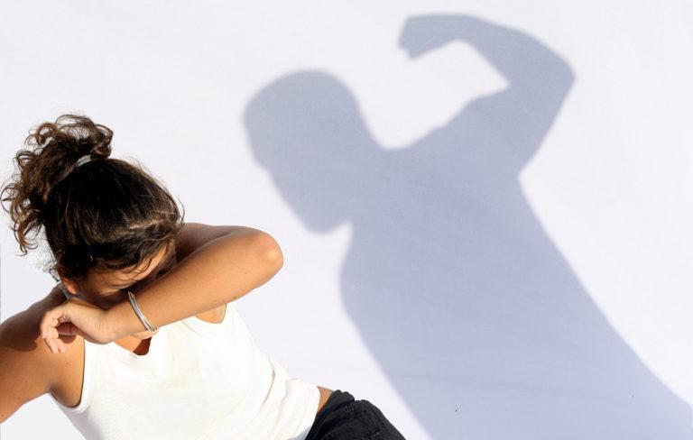 Nainen suojautuu lyönniltä, vieressä nyrkkiä heristävän miesoletetun varjo