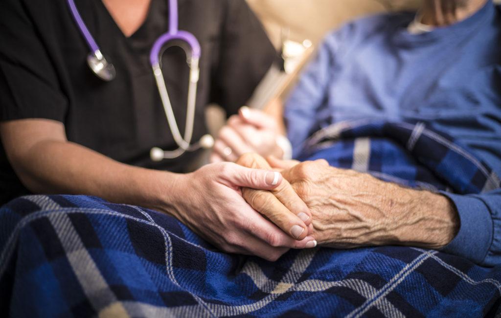 hoitaja pitää vanhusta kädestä kiinni