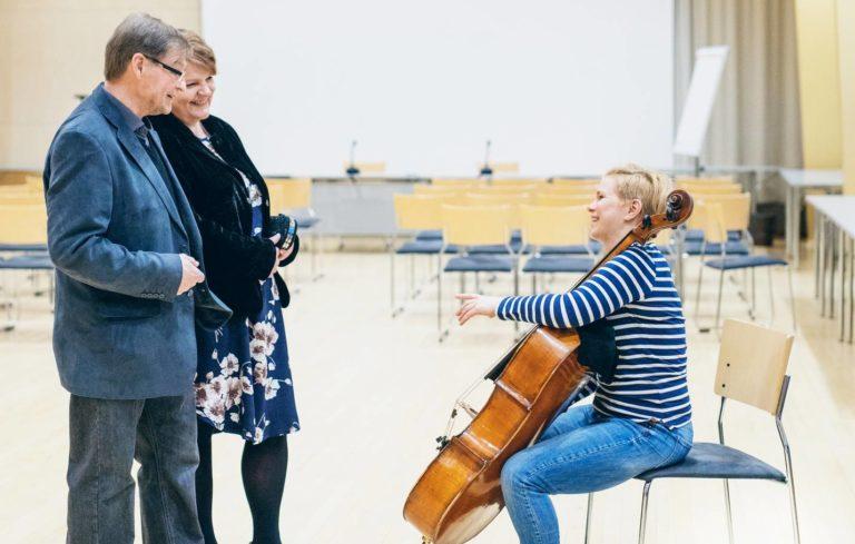 Marja-Leena Kuhanen ja Tapio Myllynen pääsivät kurkistamaan kulisseihin ennen konserttia. Sellisti Sanna Palas-Lassila lämmittelee.