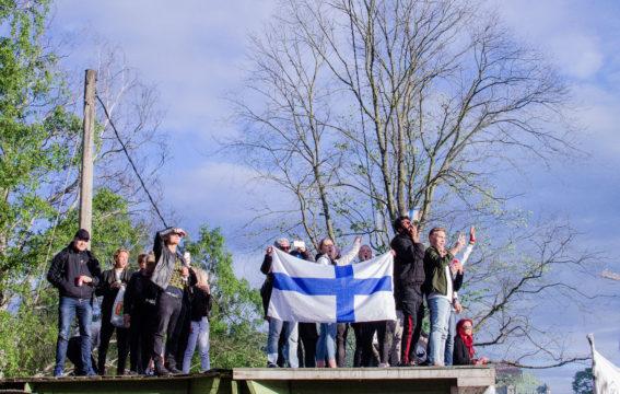 Juhlijat tähystelivät väkijoukon yli kohti lavaa jääkiekon maailmanmestaruuden kansanjuhlassa Kaisaniemessä.
