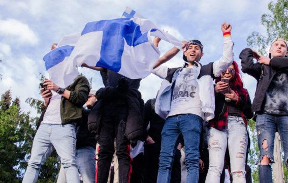 Juhlijat kiipeilivät rakennusten päälle liput liehuen jääkiekon maailmanmestaruuden kansanjuhlassa Kaisaniemessä.