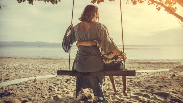 Äiti ja lapsi keinussa hiekkarannalla.