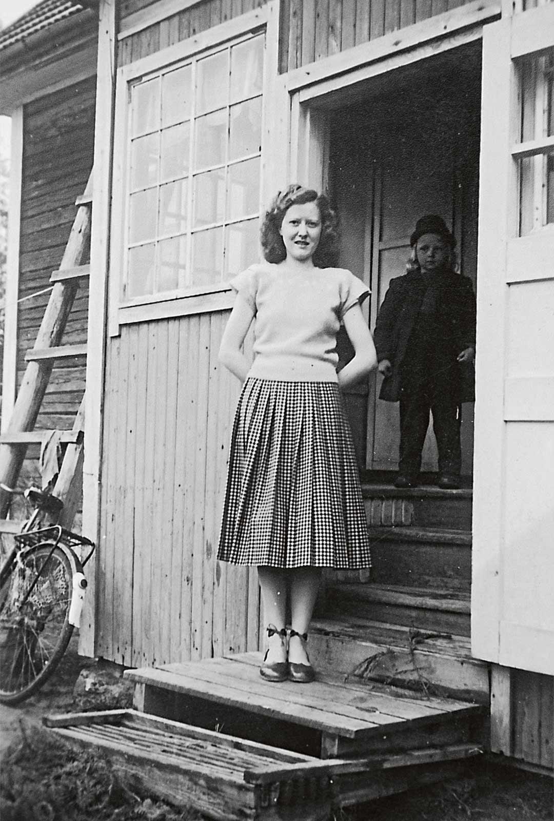 Heidi Könkään äiti lapsuudenkotinsa portailla. Vaatimaton talo rakennettiin Mänttään suon laitaan.