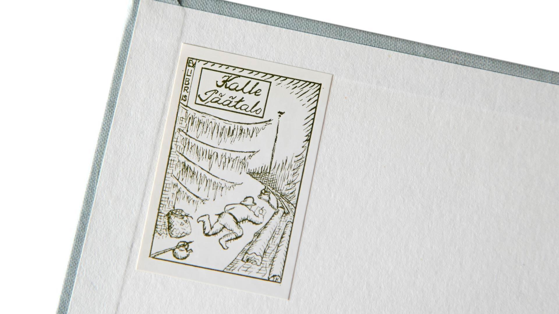 Kalle Päätalon ex libriksessä metsäjätkä kirjoittaa kynällä paperille keskellä metsää.