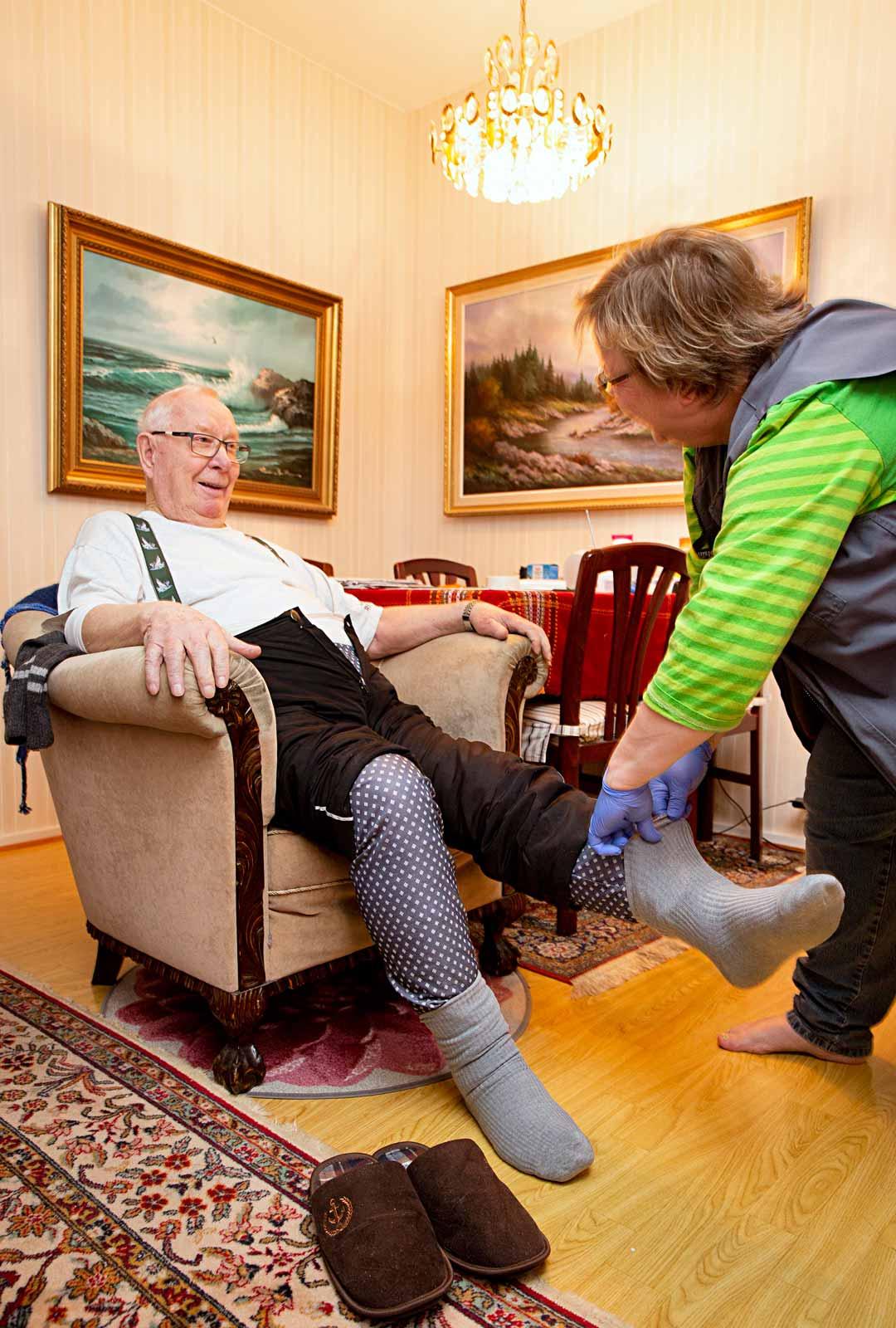 Lähihoitaja Auli Rantanen auttaa Lauri Hiltusta sukkien pukemisessa. Uintipäivinä hoitaja ei pue tukisukkia, vaan peittää katetrin aukon vedenkestävällä lapulla.