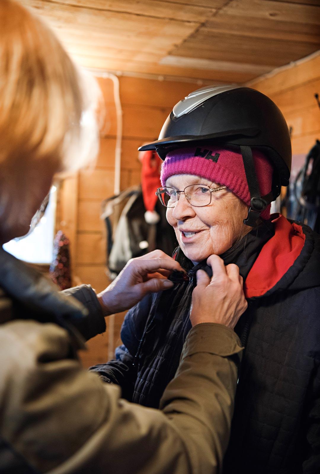 Ensin laitetaan kypärä päähän. Hetken arkailun jälkeen Irmeli muistaa, miten hevosten kanssa ollaan – rauhallisesti ja kuulostellen.