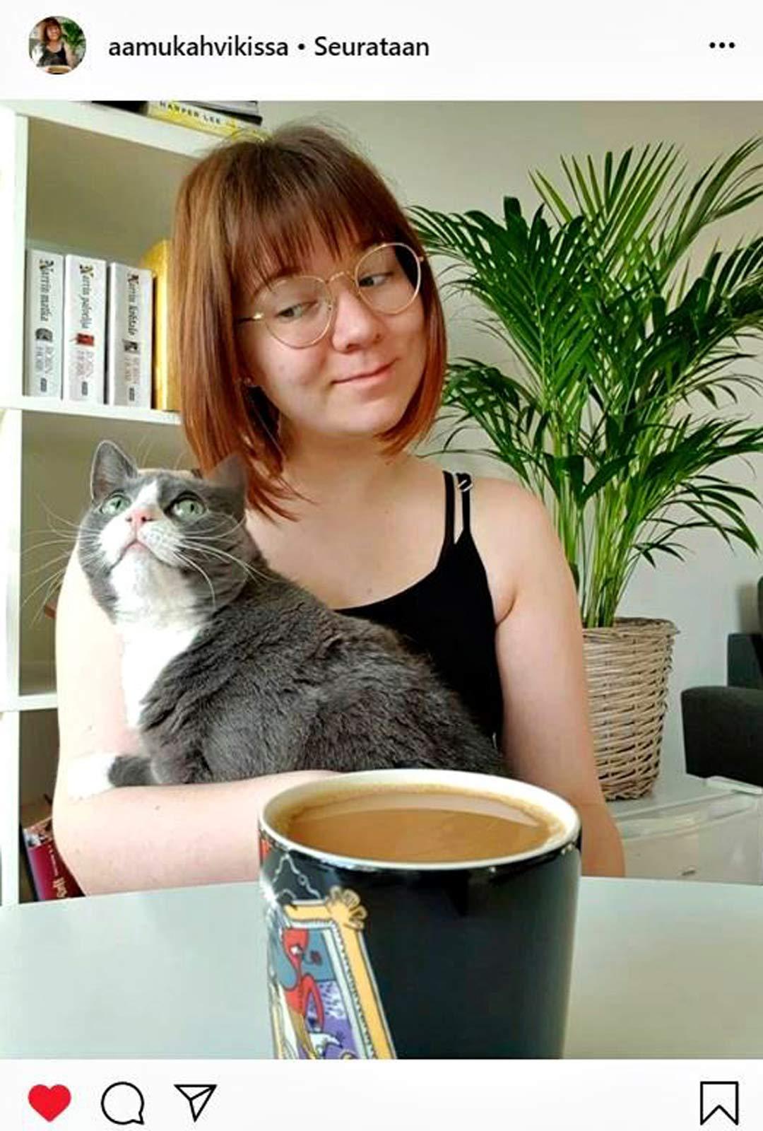Tiina Kemppaisen Instagram-kuvissa veikeäilmeinen kissa istuu emäntänsä sylissä kahvikupposen äärellä.