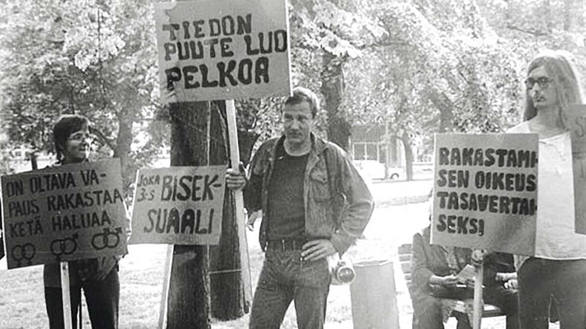 Heinäkuussa 1974 Veli (kuvassa keskellä) osallistui Setan järjestämään Suomen ensimmäiseen homojen mielenosoitukseen. Siinä puolustettiin helsinkiläisen Vanhankirkon seurakunnan nuorisotyöntekijää Seppo Kivistöä, joka uhattiin irtisanoa tehtävästään suuntautumisensa vuoksi.