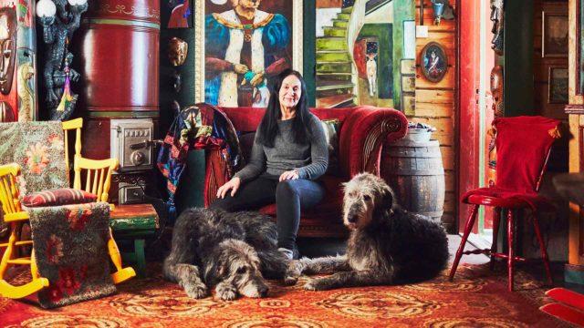 Terhi Palomaa istuu lempinurkkauksessaan salissa koirien kanssa. Abbie makaa, Tara istuu.