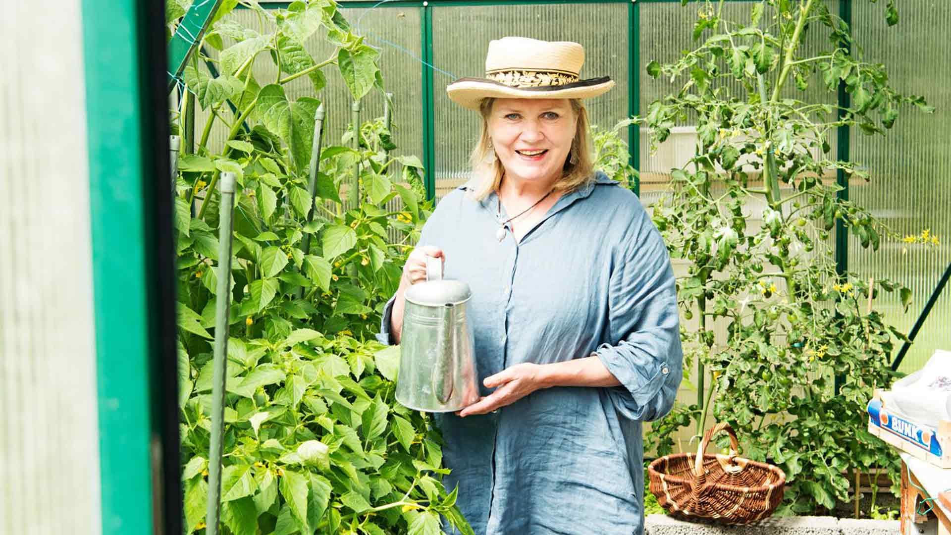 Sisko Hallavainio on onnellinen, kun saa puuhata puutarhassa sormet mullassa. Kasvihuoneessa kypsyy runsas sato.