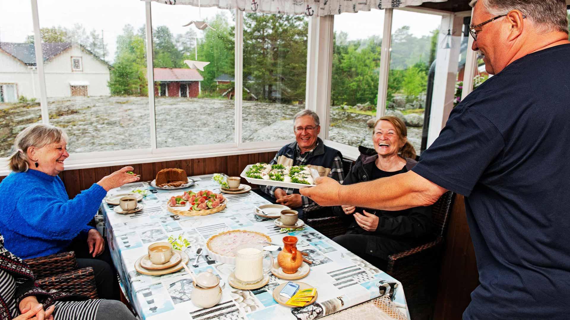 Pirjo ja Ilkka Lehdon lasikuistilla on mukavaa kahvitella ja ihailla merimaisemaa. lkka Lehto tarjoilee vieraille kalaleipiä. Pöydän ääressä Tarja Pohjola, Tuula Hynninen (kuvassa vasemmalla), Timo Pohjola ja Sirpa Ollikainen.