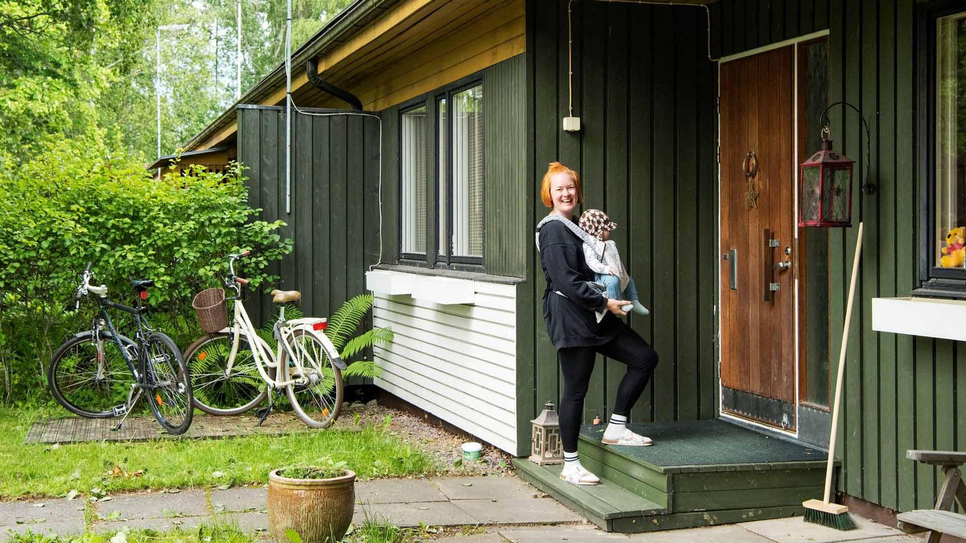 """Janette Vainio Sauli-vauvan kanssa kertoo, että he pitävät rivitaloasunnon retrotyylistä. Vainio arvostaa luonnonläheisyyttä ja omaa pihaa. """"Tämä on viihtyisä alue. Ja tämä arkkitehtuuri! Vaikka olen monet kerrat katsonut kaikki talot läpi, aina vain ihastelen niitä."""""""