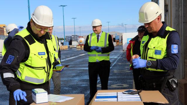 Tullin edustajat Risto Tiihonen (vasemmalla) ja Jyri Syrjänen tarkastavat tarkastavat ensimmäistä merirahtina tullutta suu- ja nenäsuojainlastia Vuosaaren satamassa.