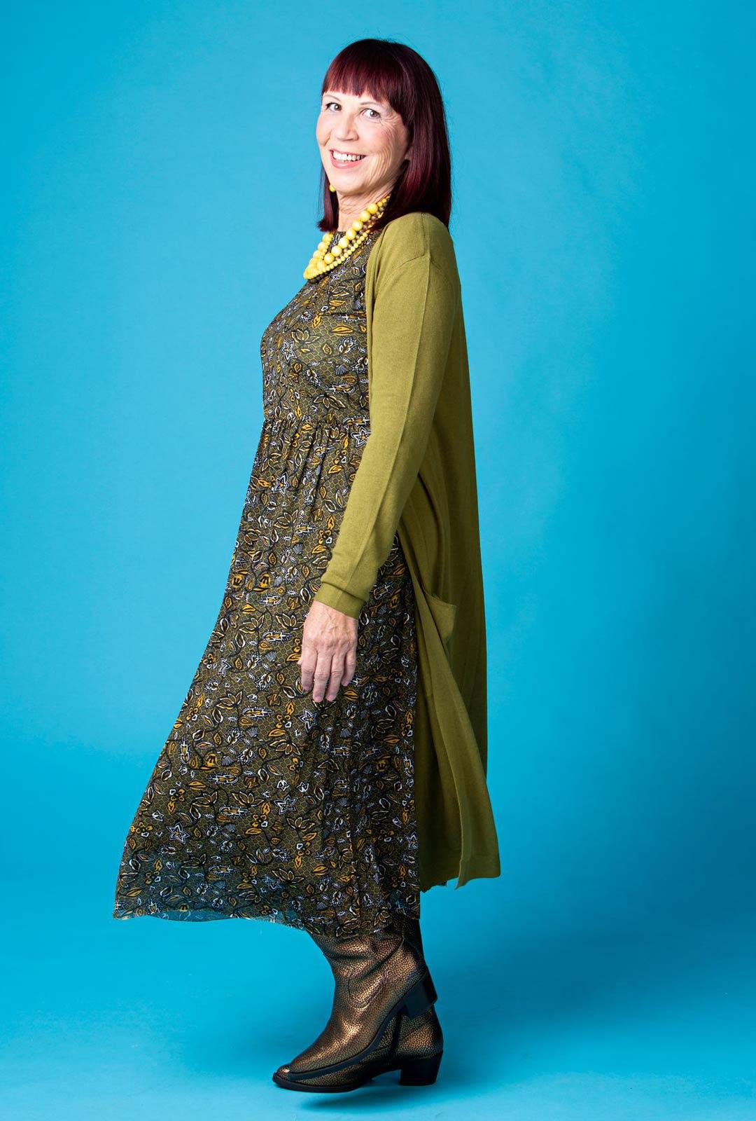 Pitkä neuletakki ja maksimekko ovat luottopari töihin. Vihreä on yksi Tuijan suosikkiväreistä. Se sopii edelleen myös tummiin hiuksiin. Pilkahdus okrankeltaista mekon kuvioissa ja koruissa kirkastaa hillityn vihreän.
