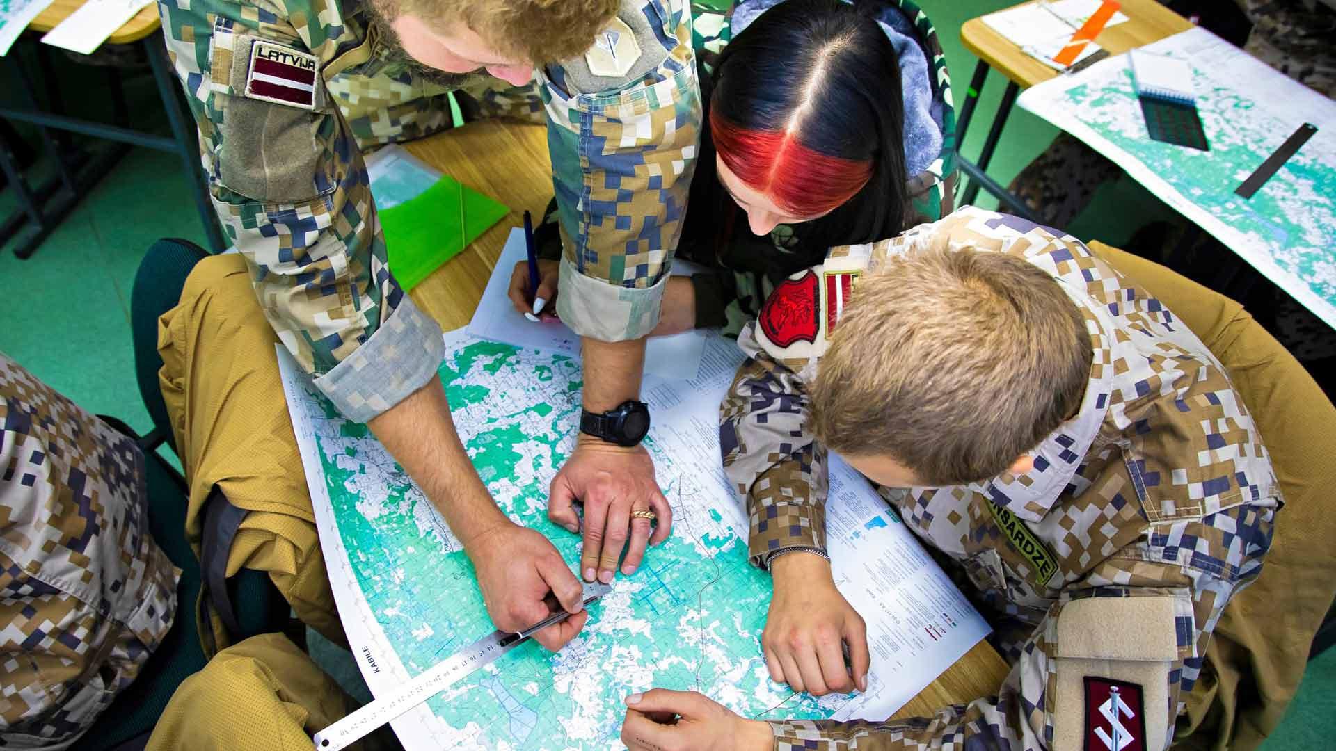 Kouluttaja Girts Skanis opettaa luokassa kartanlukutaitoja.