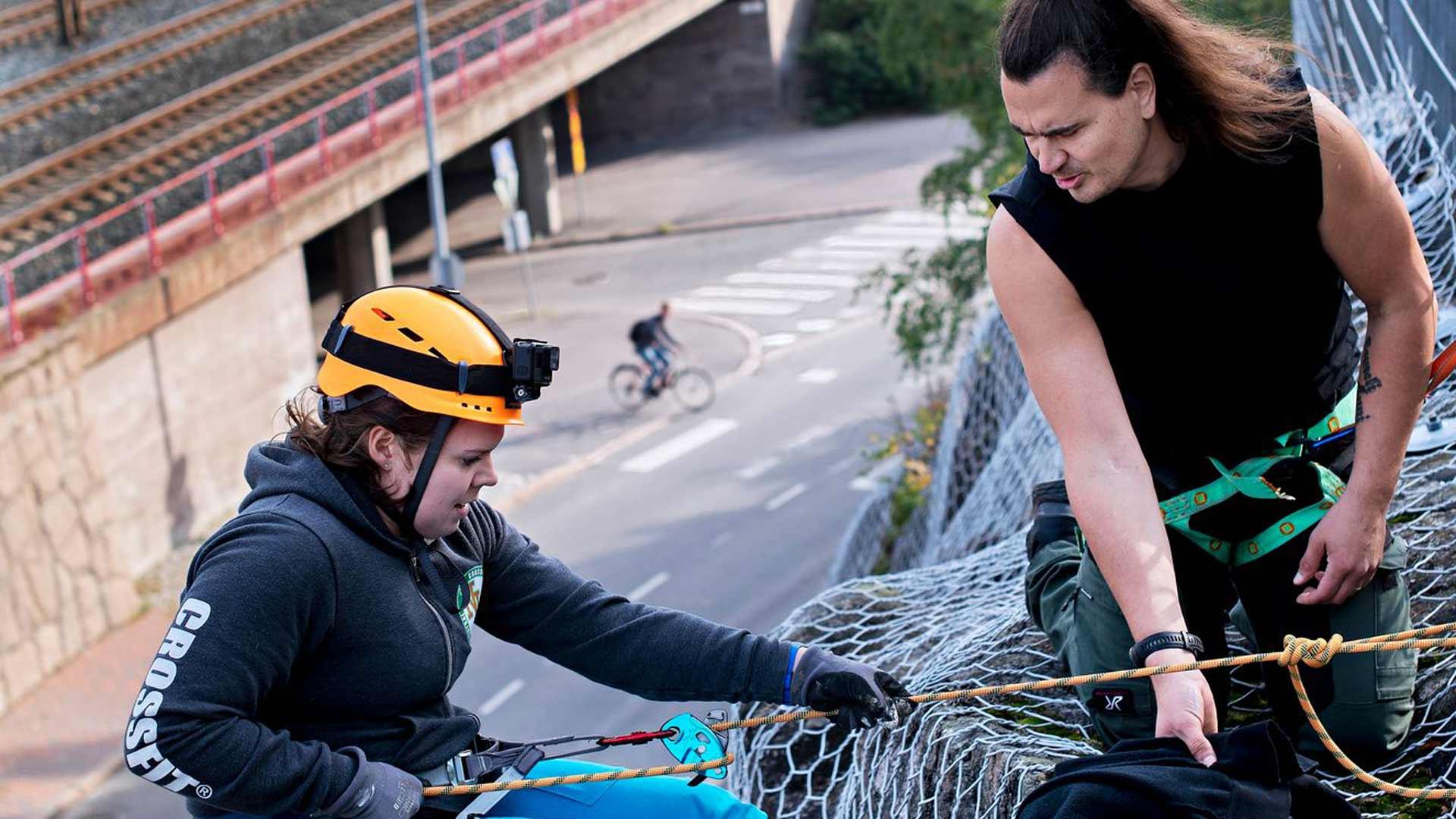 Aino Aalo laskeutuu etsimään kallioseinämän kätköä ja Mikko-Ville Toivonen varmistaa turvallisuuden.