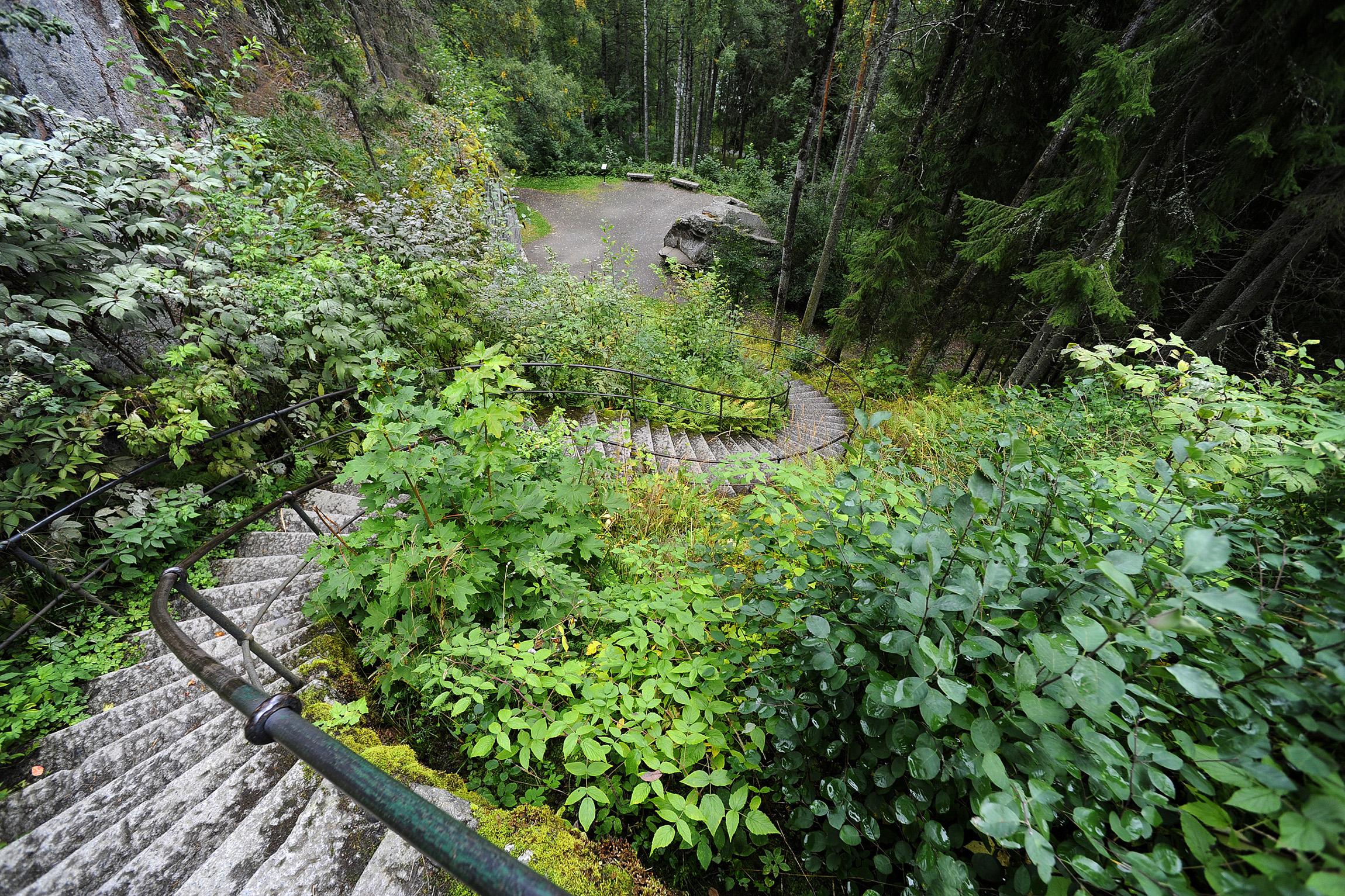 Näkötornin ja näköalatasanteen vierestä voi laskeutua jyrkkiä kiviportaita Karhuluolalle ja Aulangonjärven rantaan asti.