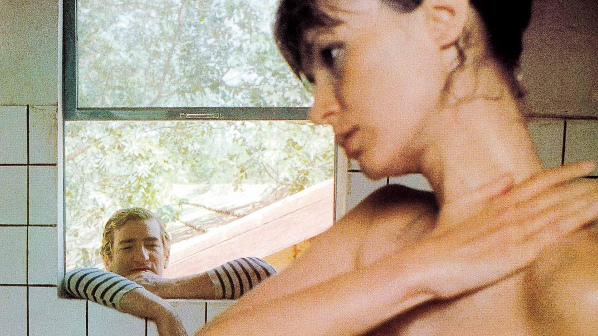 Nono (Eddy Mitchell) tirkistelee suihkuttelevaa Rose Marcaillouta (Isabelle Huppert) elokuvassa Auringonpimennys.