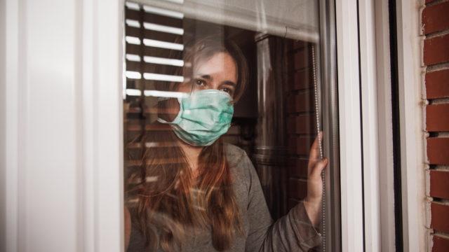Nainen ikkunalla maski päällä