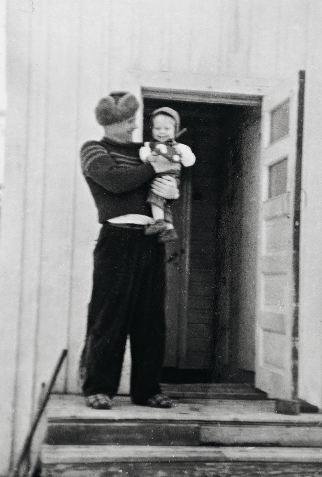Vuonna 1937 syntynyt Pentti isänsä sylissä kotitalon portailla ennen sotia.