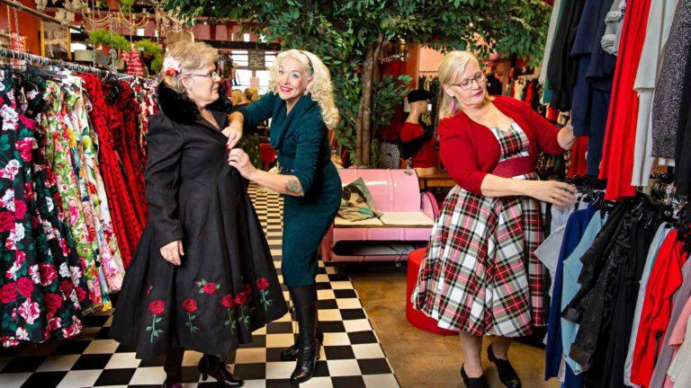 Anita sovittaa vakioasiakkaalleen Tuulalle takkia uudesta mallistosta. Tuula ja Sinikka ovat ystävystyneet Anitaan kaupassa käyntien myötä.