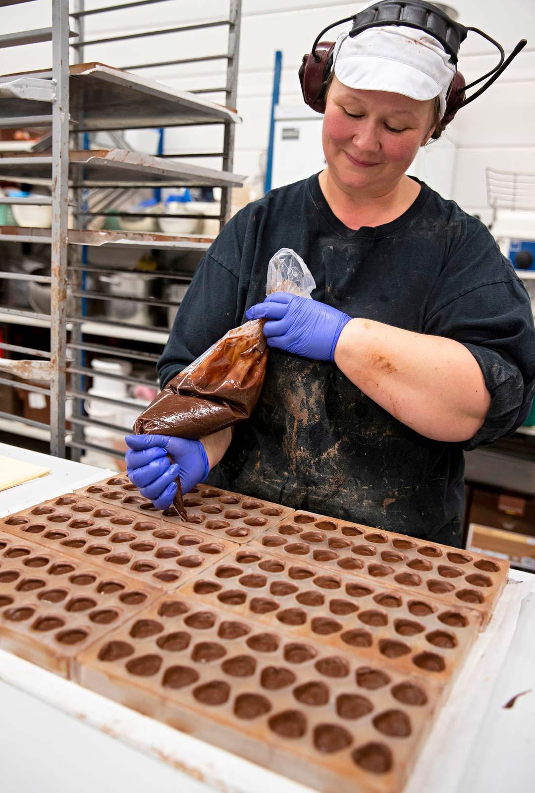 Dammenbergin suklaantekijä Marjo pursottaa mansikkatäytteisiä konvehteja.