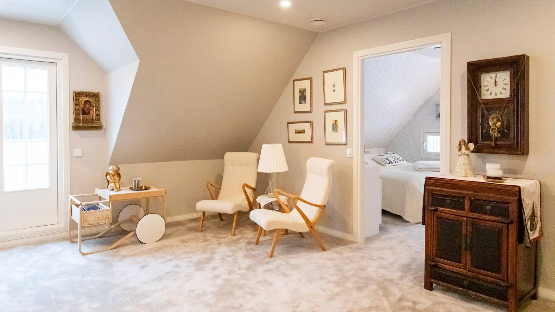 Yläkerran viihtyisästä aulasta kuljetaan makuuhuoneisiin. Taustalla näkyy vierashuone.