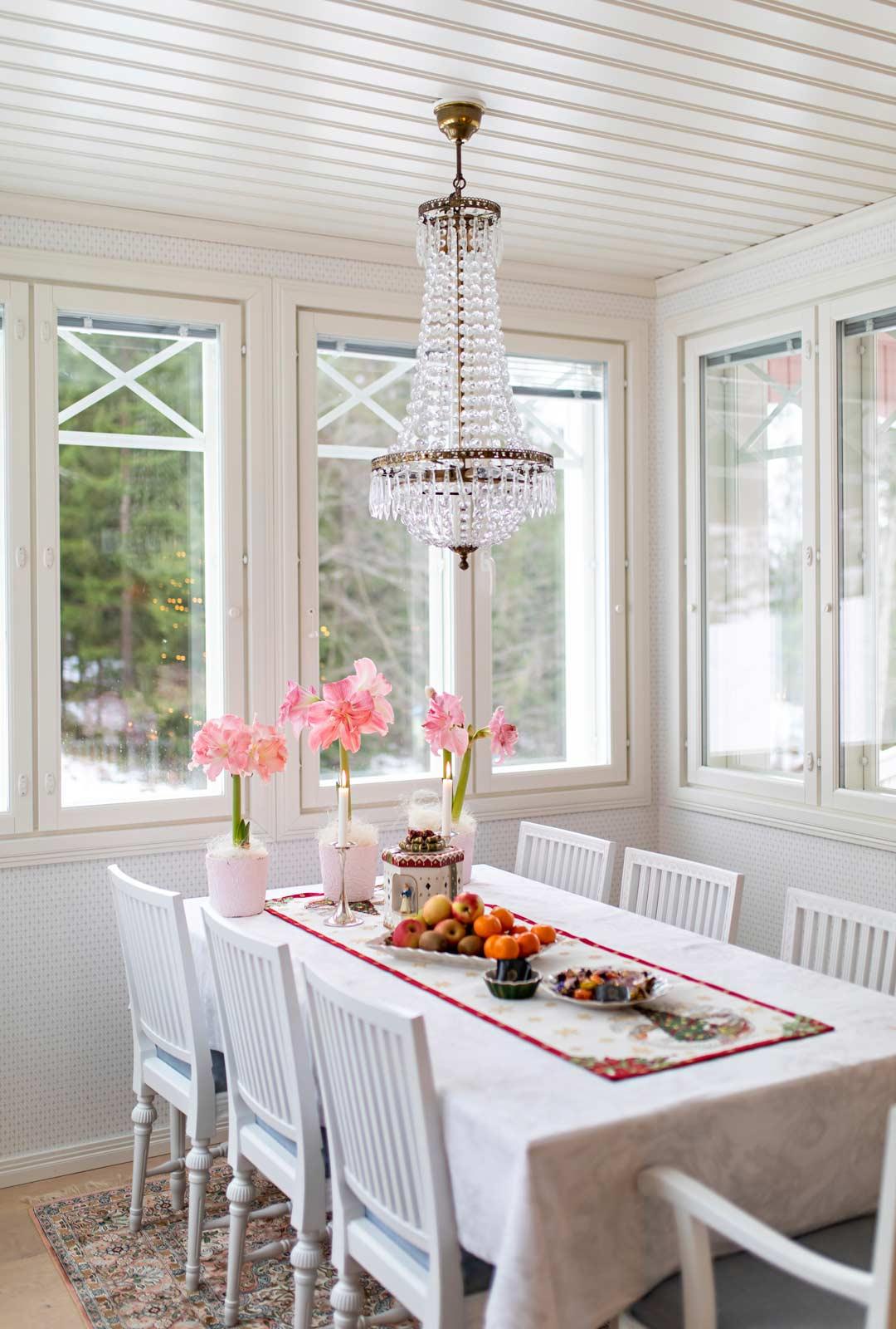 Valoisalla kuistilla on tunnelmallista ruokailla ja kahvitella. Amaryllisten väri on sama kuin talonkin, vaaleanpunainen.