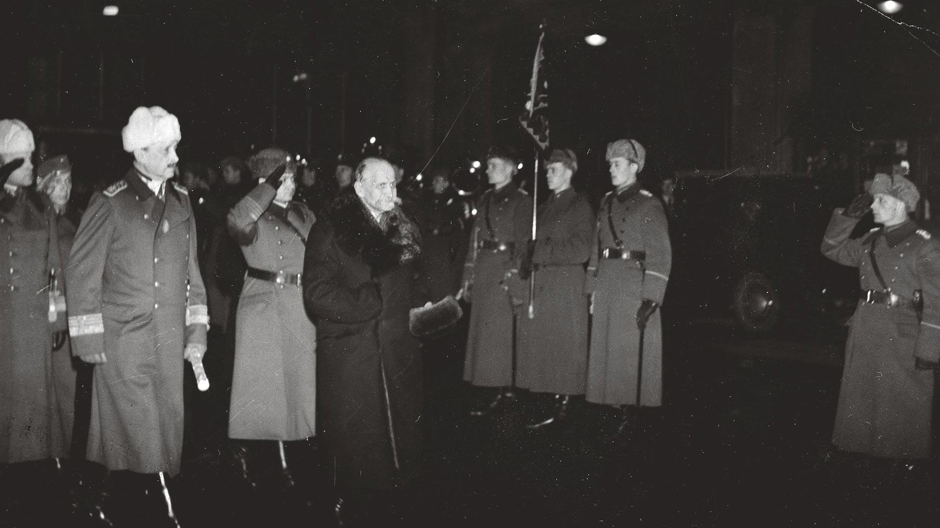 Presidentti Kyösti Kallio tarkastaa Helsingin rautatieasemalla kunniakomppanian hieman ennen kuolemaansa. Hänen oikealla puolellaan marsalkka Mannerheim, takanaan eversti Aladár Paasonen.