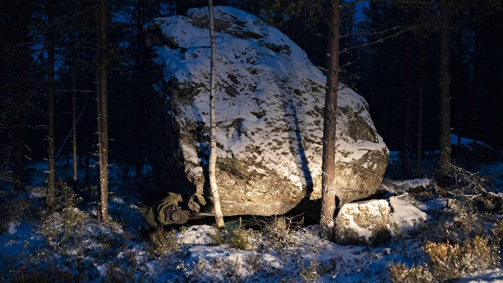Muinaisuuden jälkiä kotiseutunsa metsistä etsivä Anssi Toivanen kurkistelee Leppävirran Tilkonvuoren Jättiläisenkiven alle.