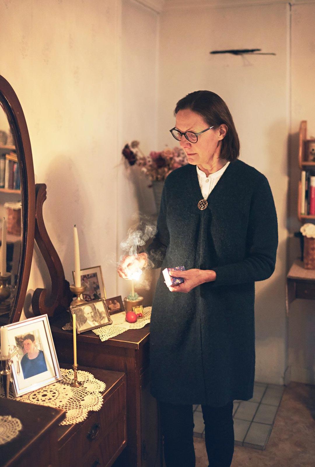 Saattohoito siskolle - Marianne Tapaninen sytyttää tuohuksen isosiskonsa Britan kuvan vierelle.