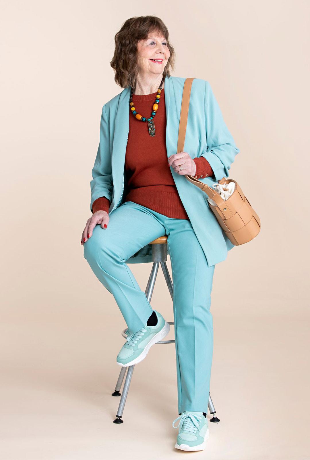 Kevään housupuvut ovat väreiltään heleitä ja mitoitukseltaan reiluja. Terrakotan ja mintun yhdistelmä tuo nuorekasta raikkautta Riitan kasvoille. Pitkään bleiseriin sopivat kapealahkeiset housut.