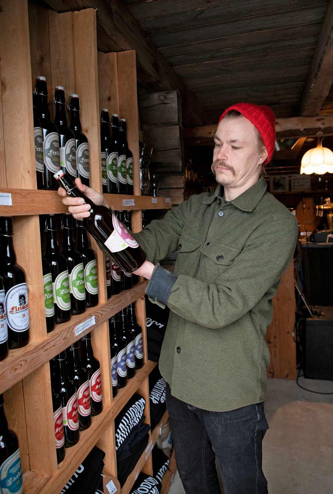 """Hailuodon Panimon ensimmäinen olut Laakeri on yhä yksi panimon myydyimmistä tuotteista. Kuvassa Kaukonen pitelee Gosea, hapanta vehnäolutta, jota on maustettu korianterinsiemenillä ja merisuolalla.""""Tällä hetkellä eniten menee Spezialia, siinä on reilummin mallasta ja humalaa"""", Kaukonen kertoo."""