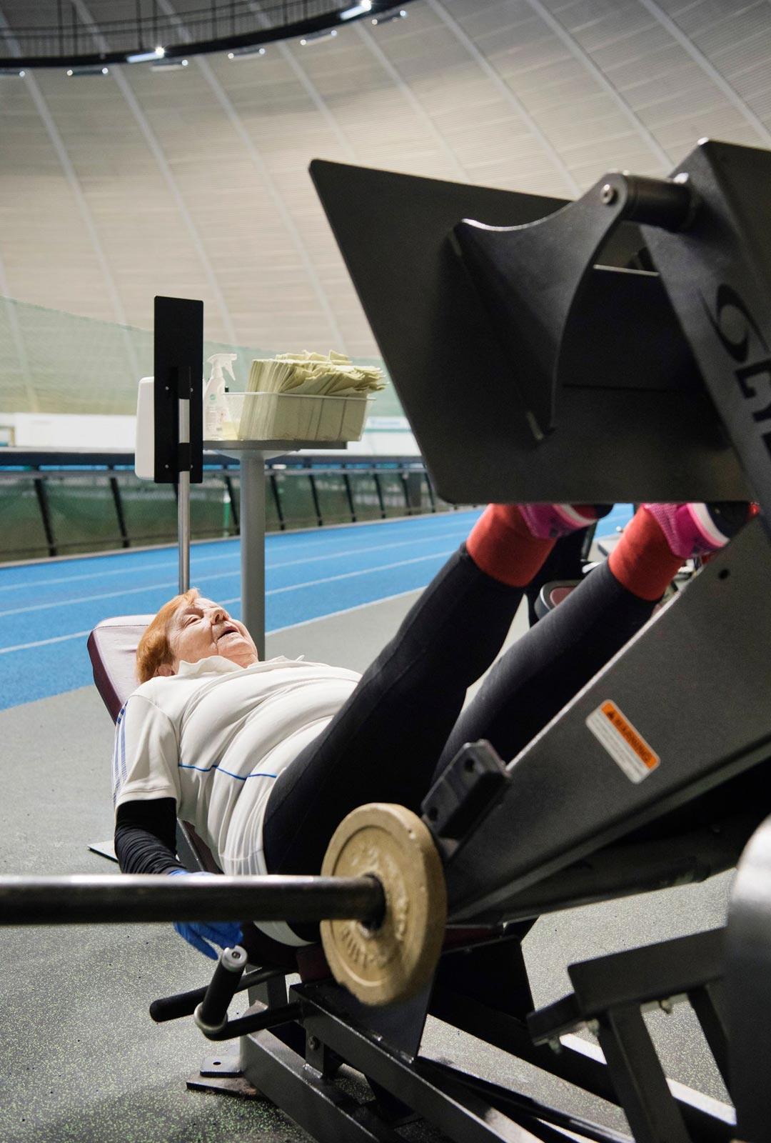 Vaijerit juoksevat ja painot kilahtelevat, kun Kyllikki treenaa jalkaprässissä.