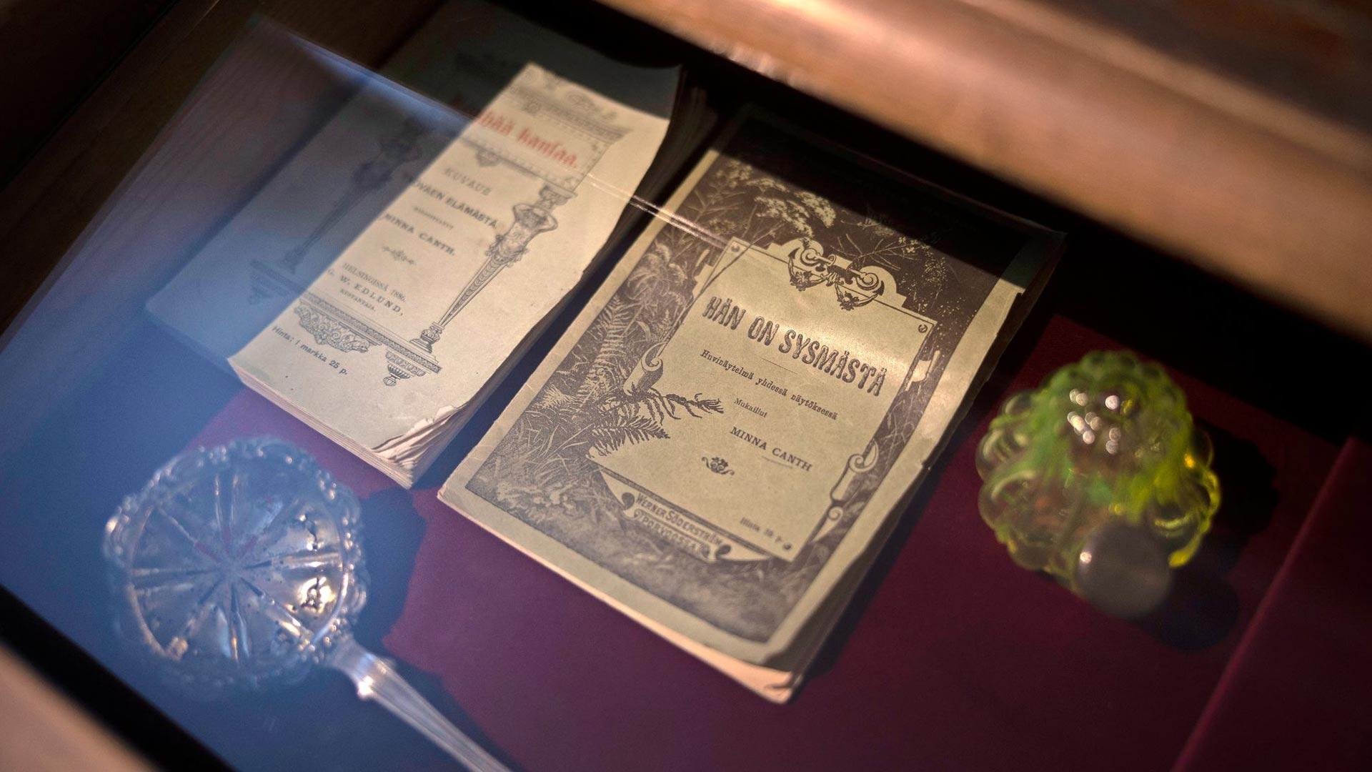 Minna Canthille kuuluneita esineitä Kuopion korttelimuseossa: alkuperäisiä näytelmävihkoja, mustepullo ja sirotelusikka.
