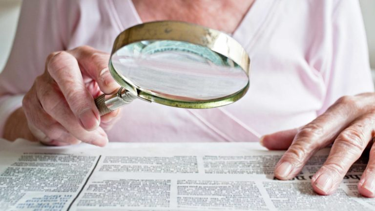 Suurennuslasi auttaa iäkästä lukemaan pientä tekstiä.