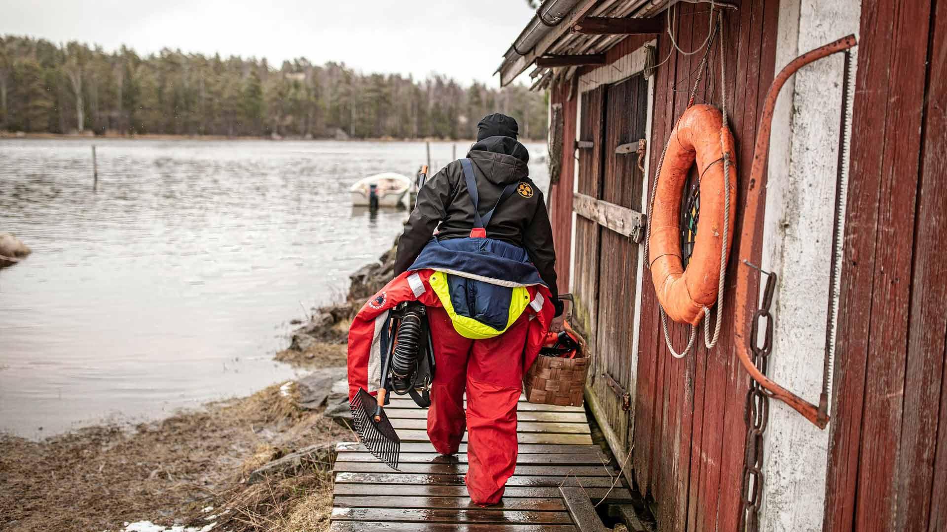 Päivän työt on tehty. Britt-Lis kantaa varusteet veneestä kotirannan vajaan.