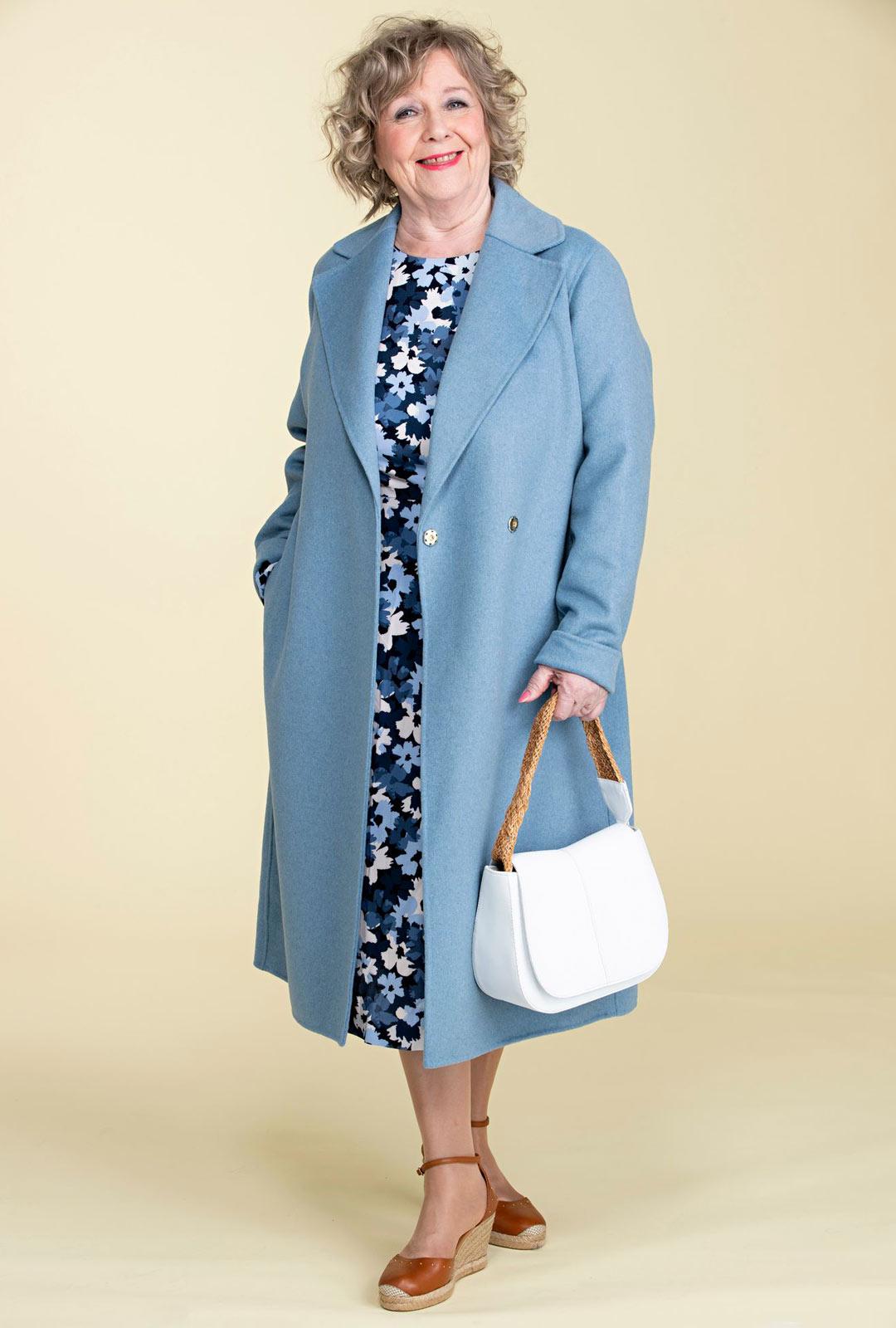 Vuorittoman takin kevyesti räätälöity linja istuu timantilla. Mekon malli on niukka ja vartaloa myötäilevä ylhäältä.