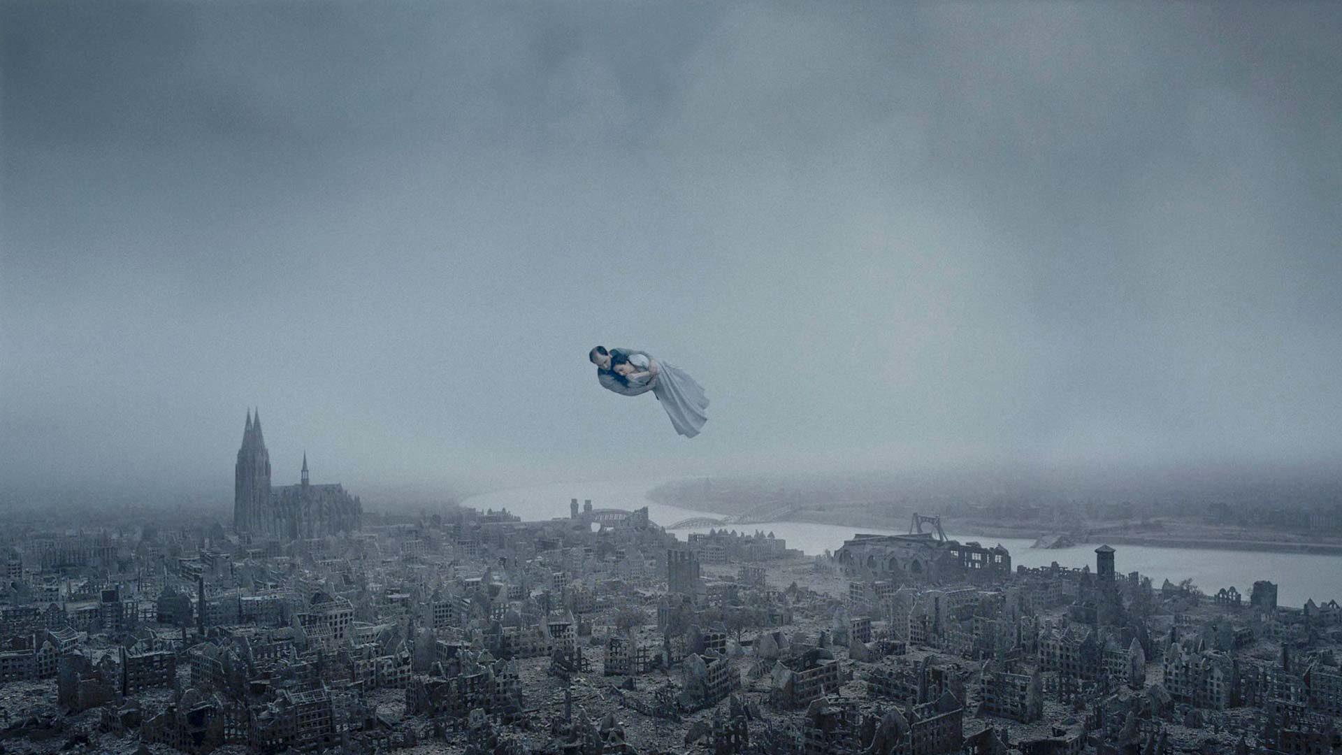 Kohti ääretöntä -elokuvassa pariskunta liitää pommitusten raunioittaman Kölnin yllä.