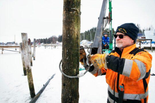 """""""Noin joka viides venepaalu täytyy talvisin siirtää"""", kertoo Tapani Johansson. Niinä vuosina, kun jäätä ei ole tarpeeksi kantamaan koneita, työ tehdään ponttonilautalta käsin. Silloin työnopeus on huomattavasti hitaampi."""