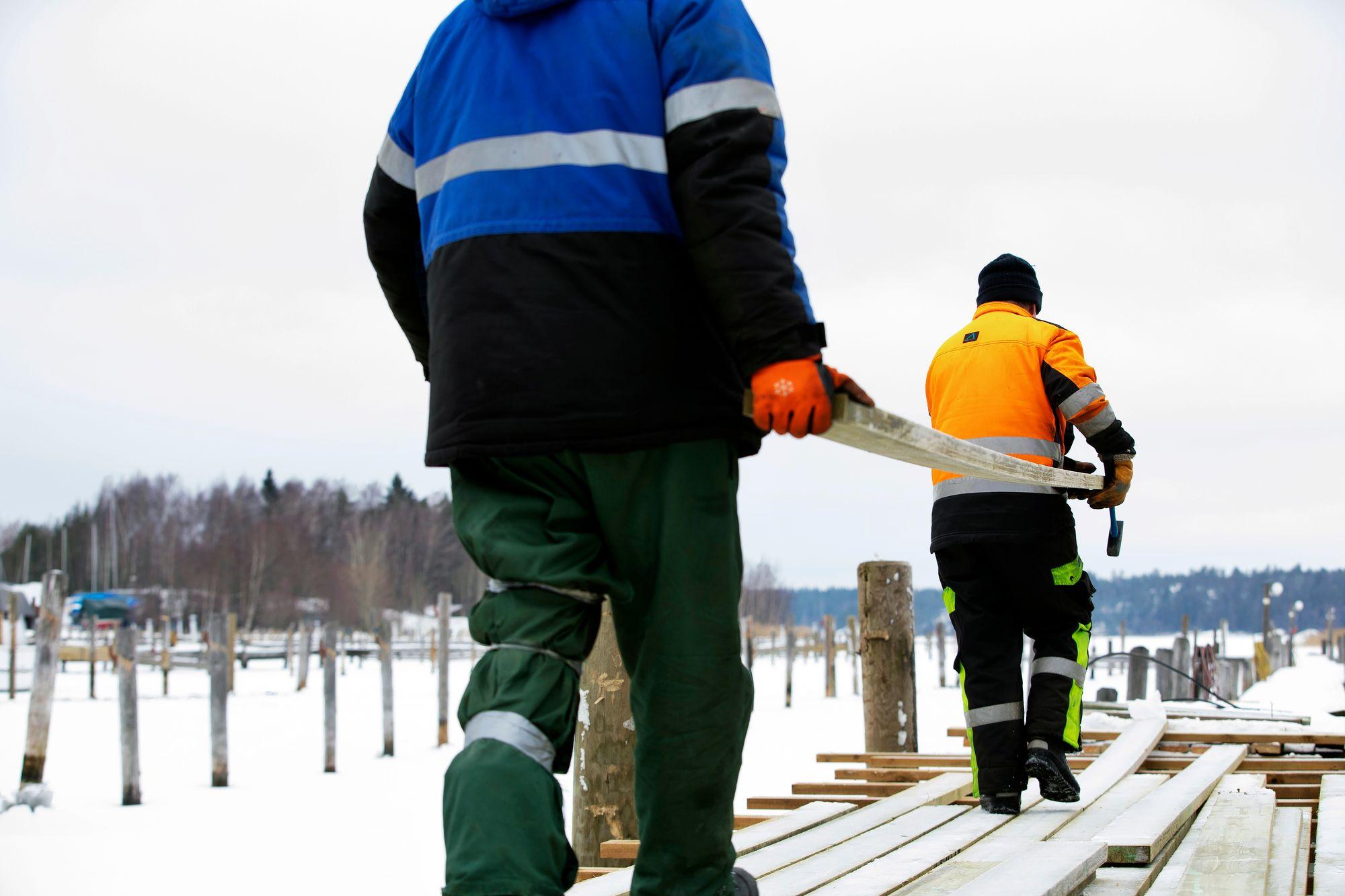 Janne Norqvist ja Tapani Johansson kuljettavat uusia lautoja laituriin, joka vaatii kunnostusta.