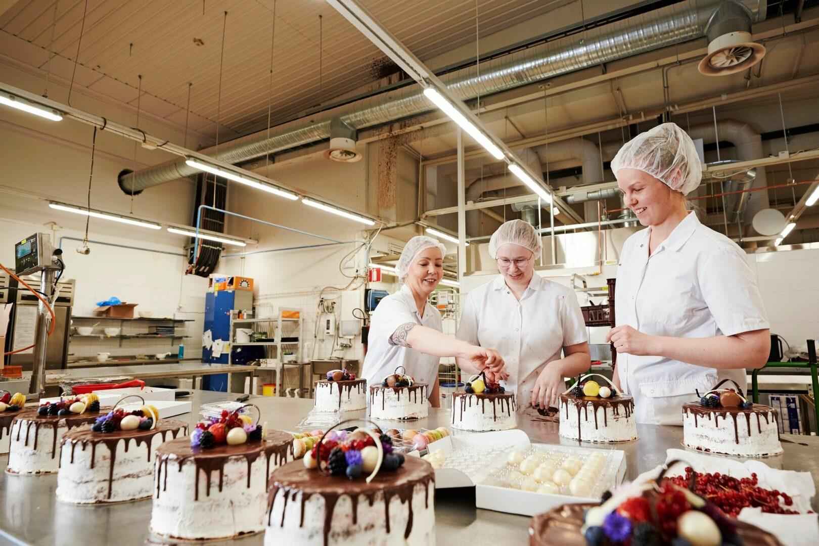 Tiia Bisterin, Anni Löövin ja Annukka Hietamäen aamun urakkana on koristella juhlakakut valmiiksi aamun toimituksia varten.