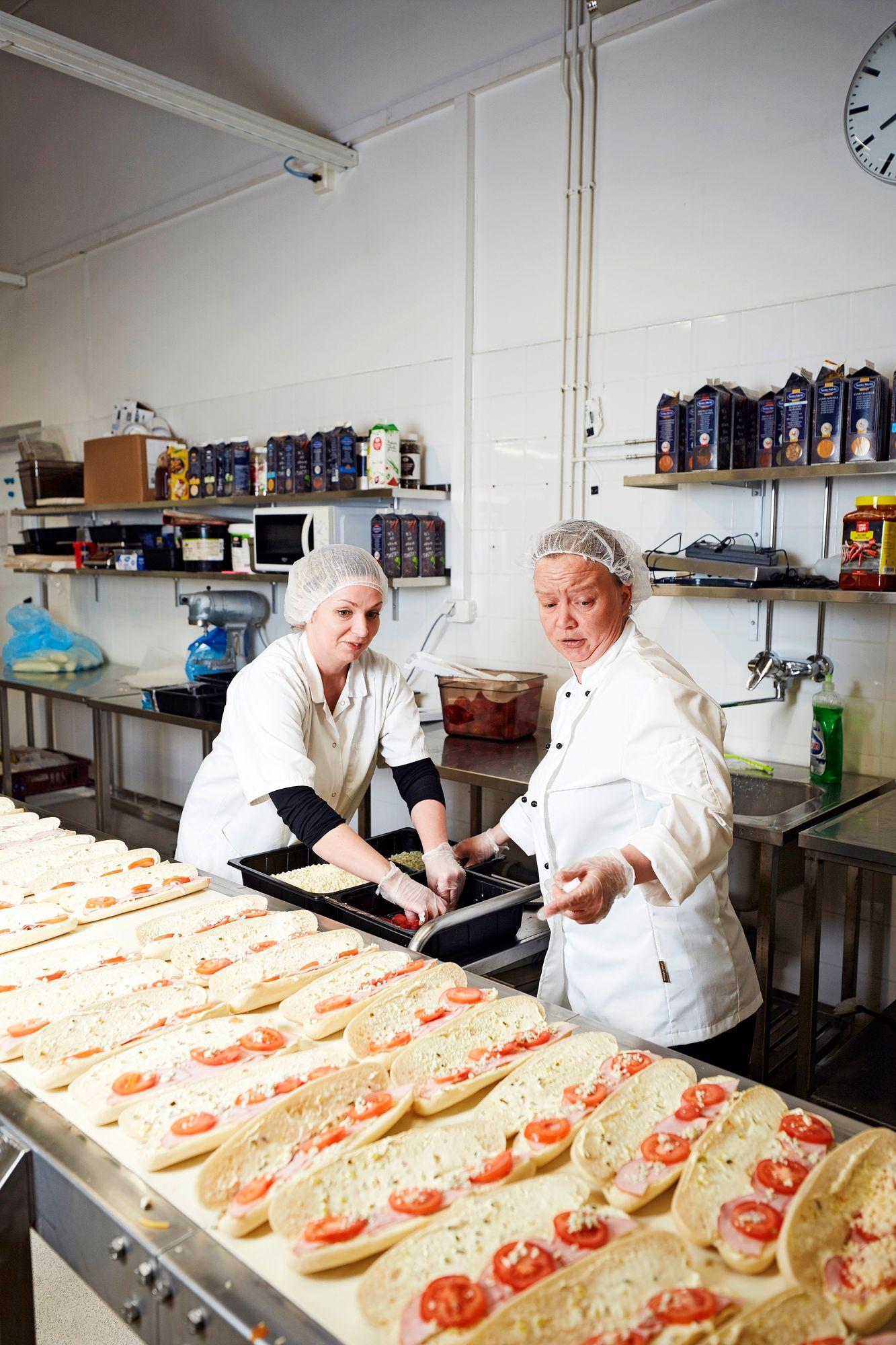 Paninien valmistus sujuu joutuisasti yhteispelillä. Mari Heiskanen (vas.) ja Tanja Tyni pitävät huolen, että jokainen panini sisältää sitä, mitä pitääkin. © Sara Pihlaja